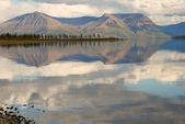 Lake Lama and reflected in the water clouds and mountains of the — Stock Photo