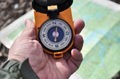 The compass in his hand outdoors. — Stock Photo
