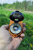Compass in hand, against the background of blooming meadows.  — Stock Photo