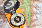 Open compass on the maps. — Stock Photo