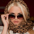 A beautiful girl in a shawl with leopard printom is surprised - Stock Photo