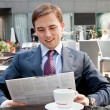 Businessman reading a newspaper in a cafe and happy news — Stock Photo