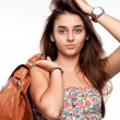 Portrait of a girl with a bag and hand near her head — Stock Photo