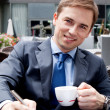 portrait of a young businessman signing documents in a cafe — Stock Photo
