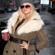 Girl drinks coffee in the street in a jacket with fur — Stock Photo