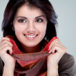 Portrait of a smiling girl holding a scarf around the face — Stockfoto