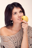 Portrait of a girl holding an apple near the lips (retro) — Stockfoto