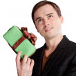Portrait of a man holding a gift and start thinking about what you — Stock Photo
