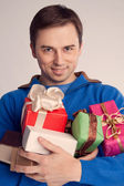Portrait of a man holding a lot of gifts in the hands of (retro) — Stock Photo