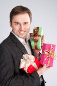 Portrait of a man holding a lot of gifts in her arms — Stockfoto