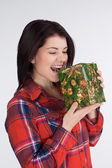 Girl in a plaid shirt bite gift — Stock Photo