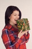 Girl in a plaid shirt bite gift (retro) — Stock Photo