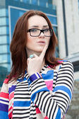 Girl in glasses on a background of the building with his finger near lips — Stock Photo