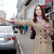 Girl in coat and catches a taxi kofem — Stock Photo #47286949