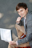 Businessman reading a newspaper on a park bench — Stock Photo