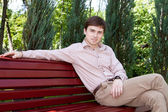A young man sitting on a bench waiting for someone — Stock Photo