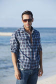 Man wearing sunglasses and standing on the beach — Stock Photo