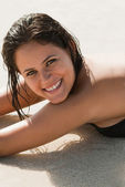 Close up of woman lying on the sand looking at camera — Stock Photo