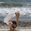 Woman practicing yoga on the beach — Stock Photo