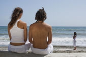 Rear view of a couple looking at a woman doing yoga on the beach — Stock Photo