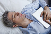 Man sleeping on bed with holding a digital tablet — Foto Stock