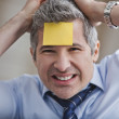 Portrait of businessmwith adhesive note on forehead — Stock Photo #22110181