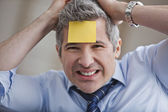 Portrait of a businessman with adhesive note on forehead — Stock Photo