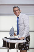 Portrait of a businessman smiling while ironing pants — Stock Photo