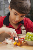 Boy making fruit salad — Stock Photo