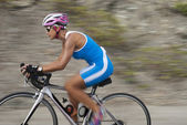 Female cyclist riding a racing bicycle — Foto Stock