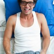 Stock Photo: Happy young mwith glasses in bed