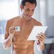 Man Wrapped in Towel holding a cup of coffe and tablet — Stock Photo