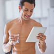 Man Wrapped in Towel holding a glass of water and tablet — Stock Photo #25693397