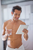 Man Wrapped in Towel holding a glass of water and tablet — Stock Photo