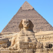 Great Sphinx of Giza against the Pyramid of Khafre - Stock Photo