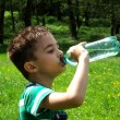 Tired child drinks water — Stock Photo