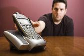 Man reaches for a modern cordless phone — Stock Photo