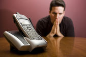 Man praying for the phone to ring — Stock Photo