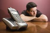 De mens is verveeld wachten voor de telefoon ring. — Stockfoto