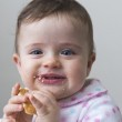 Messy, happy little girl eating a cookie — Stock Photo #18951299
