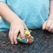 Young boy picks up multicoloured playdough — Stock Photo #18953677