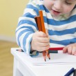 Young boy draws with three pencils - Stock Photo