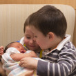 Stock Photo: Twin boys meet their baby sister