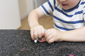 Toddler playing with multicoloured playdough on kitchen bench — Stock Photo