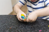 Toddler playing with multicoloured playdough — Stock Photo