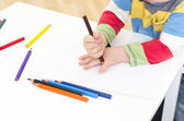 Young boy draws around his hand — Stock Photo