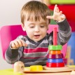 Young boy plays with wooden stacking blocks — Stock Photo