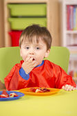 Young boy eating fruit in a nursery room — Stock Photo