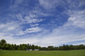 Huge sky and green field — Stock Photo