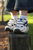 The shoes of a boy standing on a post — Stock Photo